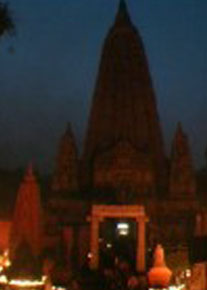 """Coverbild des Films """"Drei Buddhisten vier Wahrheiten"""" - ein buddhistisches Glaubenshaus bei Nacht beleuchtet von Kerzen"""