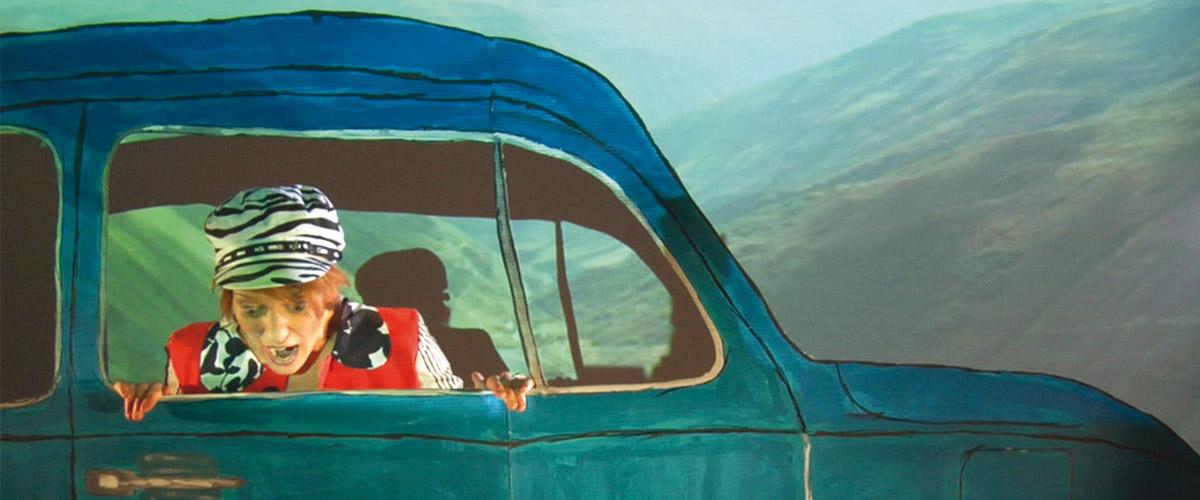 Christina Zurbrügg in einem blauen Auto während Sie erschrocken aus dem Beifahrerfenster schaut